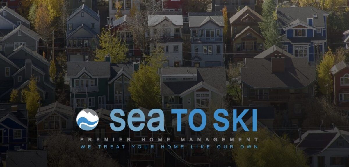 A neighborhood of colorful houses and trees with Sea to Ski logo.