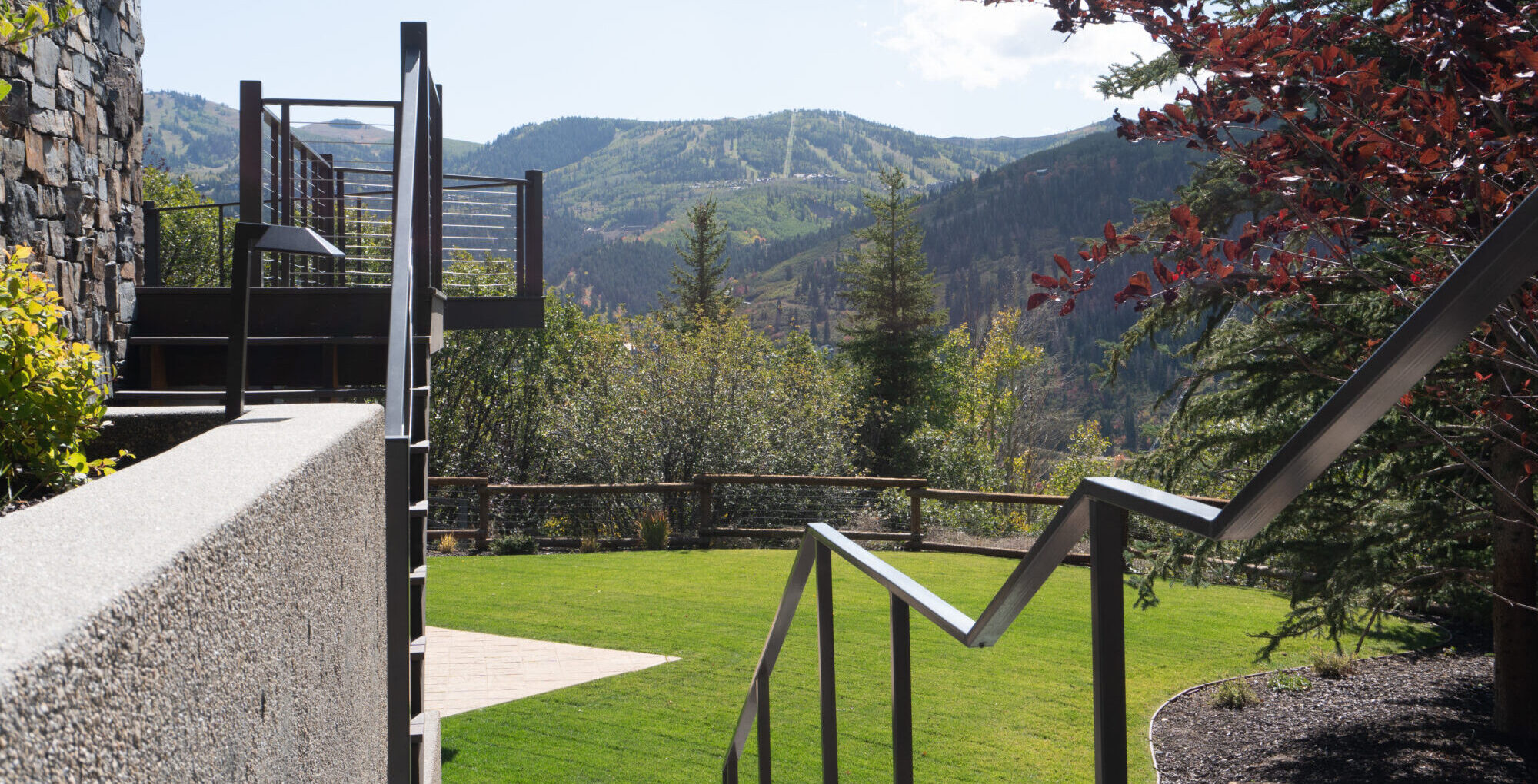 Outdoor stairs and railing leading to grass lawn overlooking mountains.