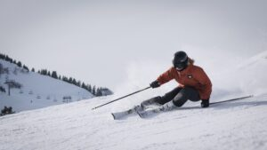 person skiing down a slope with mountain and chairlift in the background